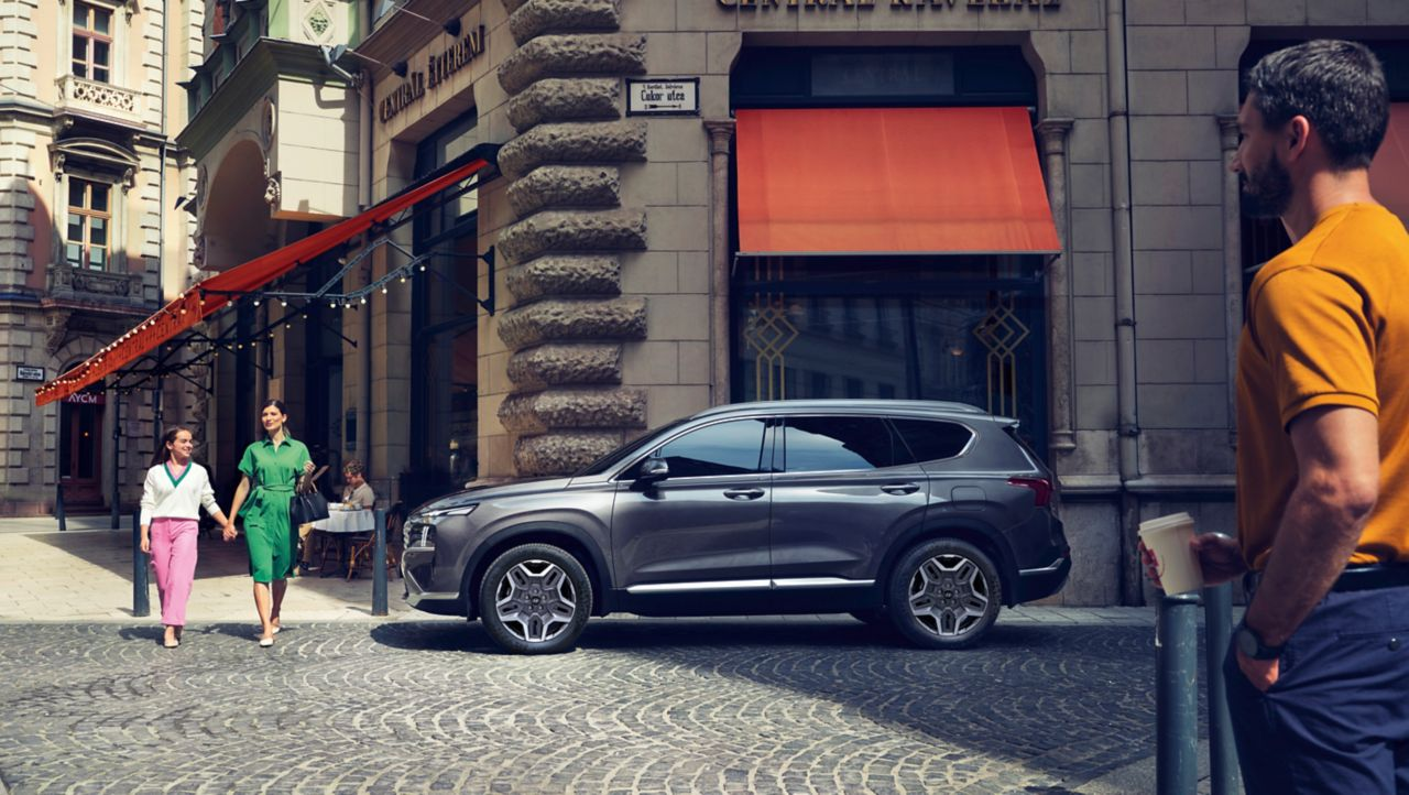 The new Hyundai Santa Fe Hybrid 7 seat SUV in grey parked on a city street.